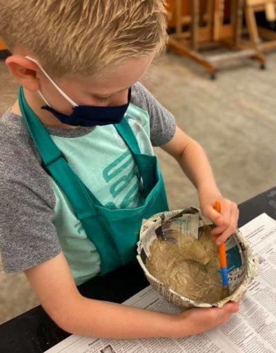 boy painting pottery